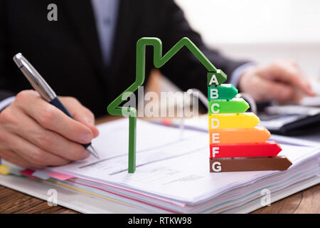 Close-up Of House Model Showing Energy Efficiency Rate In Front Of Businessperson's Hand Using Calculator - Stock Photo