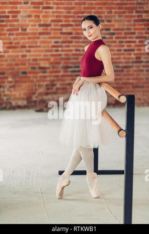 relaxed positive ballerina leaning on the barre and looking at the camera, full length photo.free time, spare time - Stock Photo
