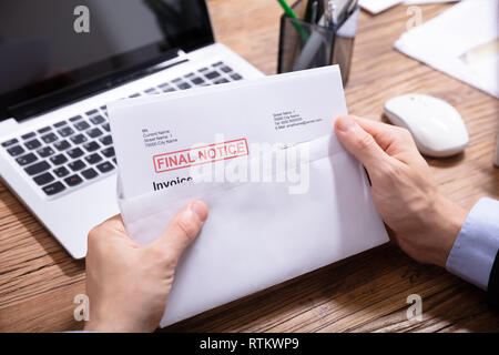 Close-up Of A Person's Hand Opening The Envelope With Final Notice Invoice In It - Stock Photo