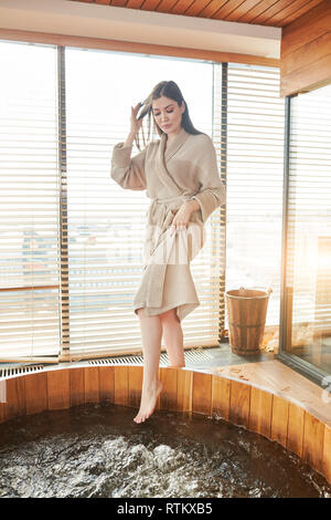 Relief after hard working stressful day. Beautiful woman, dressed in soft bathrobe testing the water before she comes into warm whirlpool, relaxing in - Stock Photo