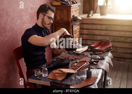 handsome guy using a shoe brush. side view photo - Stock Photo