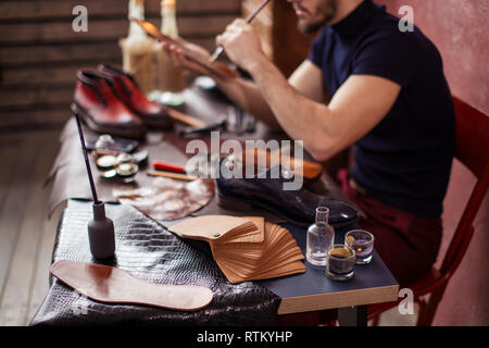 close up cropped photo. man painting with a tip of the brush, focus on the cloth, leather - Stock Photo