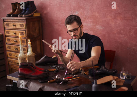 shoe designer concentrated on working with a brush. close up photo. - Stock Photo