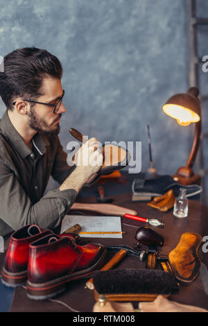 accurate working process in the shoe shop. close up side view photo. - Stock Photo