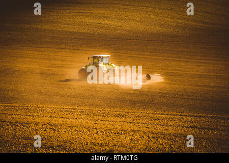 Tractor during autumn work in the fields of South Moravia at sunset - Stock Photo