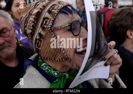 A protester seen chanting slogans while holding a placard during the protest. Feminist protest against racism in front of the Immigrant detention centre (CIE) in Aluche, Madrid. - Stock Photo