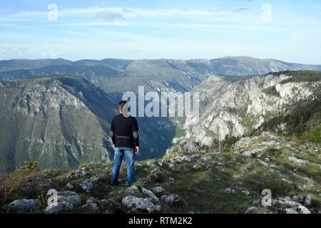 Young man stands in the edge of Tara Canyon and Tara River - Durmitor National Park. Near Zabljak, Montenegro. - Stock Photo
