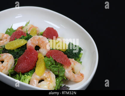 prawns and citrus fruits salad in a serving bowl - Stock Photo