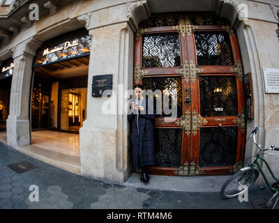 BARCELONA, SPAIN - NOV 13, 2017: Young stylish woman smoking and using the mobile phone smartphone near the entrance of the luxury Massimo Dutti fashion store on Avenue Diagonal - Stock Photo