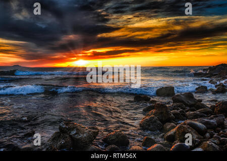 Bright sunset under the storm sea with waves splashes - Stock Photo