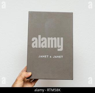 PARIS, FRANCE - DEC 18, 2017: Man holding cardboard box of Italian Janet Janet against white background - Stock Photo