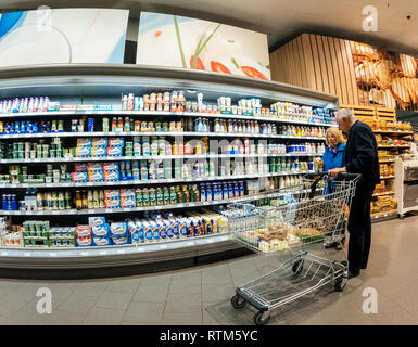 FRANKFURT, GERMANY - MAY 3, 2017: Senior couple with supermarket cart choosing the right diary products - Butter, Butter and butter blends, Cheese, Natural cheese products, Cultured Dairy, Yogurt, - Stock Photo