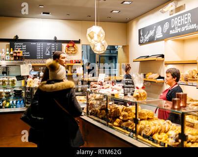 STRASBOURG, FRANCE - NOV 21, 2017: Couple buying freshly baked kougelhof cakes and bread in an German artisan bakery Dreher in central Strasbourg, Alsace - Stock Photo