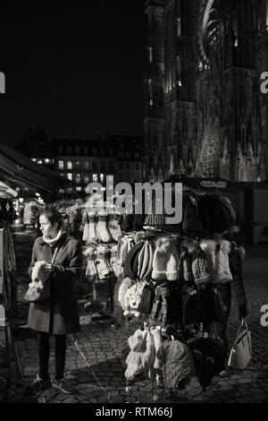 STRASBOURG, FRANCE - NOV 21, 2017: Female woman choosing knitted woolen hats and socks in PLace de la Cathedrale a day before Christmas Market starts - black and white image - Stock Photo