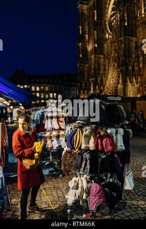STRASBOURG, FRANCE - NOV 21, 2017: Female woman choosing knitted woolen hats and socks in Place de la Cathedrale a day before Christmas Market starts  - Stock Photo