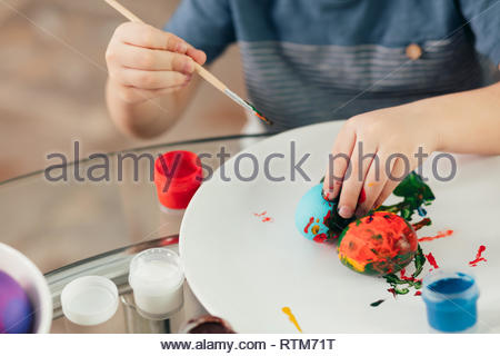 Home made Easter decorations and little helper. Selective focus of small hands of a boy covering boiled eggs with colourful paints on white plate - Stock Photo