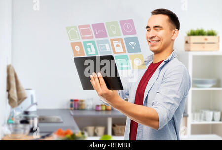 happy young man with tablet computer in kitchen - Stock Photo