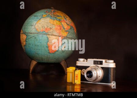 Horizontal shot of a vintage camera, film, yellow metal canister, and world globe on a brown background with copy space. - Stock Photo