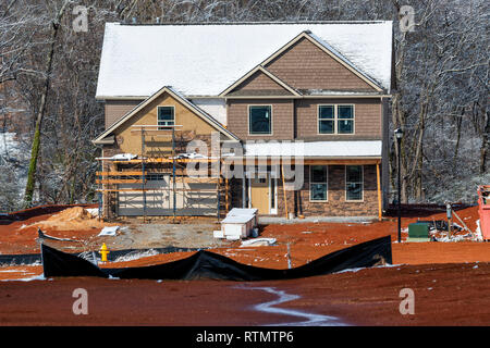 Horizontal shot of a winter two-story home construction site.  There is snow on the roof and the trees behind the house under construction. - Stock Photo