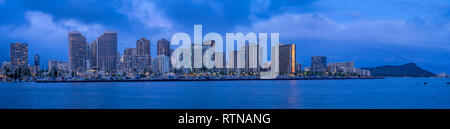 Waikiki skyline panorama from the Ala Moana beach park at night. - Stock Photo