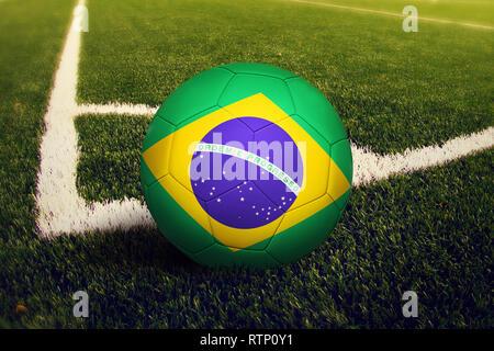 Brazil ball on corner kick position, soccer field background. National football theme on green grass. - Stock Photo