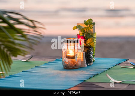 Candle on a table in sunset view restaurant on Koh Chang island, Thailand - Stock Photo