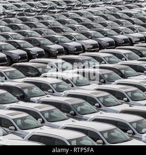 Row of new cars for sale in port. New automobiles background - Stock Photo
