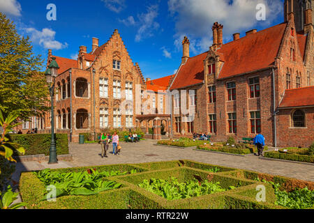 25 September 2018: Bruges, Belgium - People strolling in the courtyard of the medieval St John's Hospital in Bruges, Belgium, on a glorious autumn day - Stock Photo