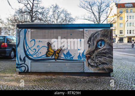 Berlin Wilmersdorf..Paintings & artwork disguise & decorate utility boxes in a suburban street. A cat looking at a butterfly - Stock Photo