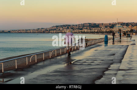NICE, FRANCE - OCTOBER 30, 2014: Old man walking along the Promenade des Anglais in Nice morning - Stock Photo