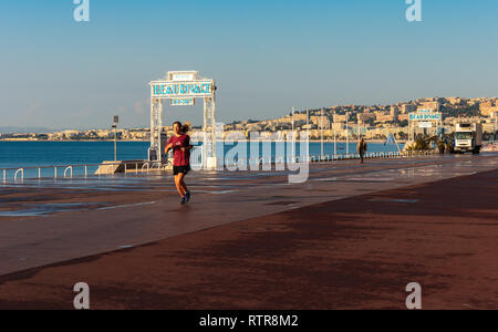 NICE, FRANCE - OCTOBER 30, 2014: Young girl jogging on the Promenade des Anglais - Stock Photo