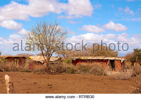 View of the Masai village with old clay huts. Poverty, misery and despair, living in Africa - Stock Photo