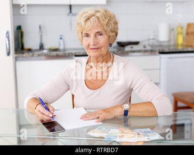Positive senior woman counting her expenses sitting at the kitchen table and using smartphone - Stock Photo