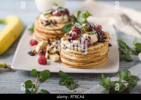 Beautiful and delish dessert, fresh pancakes with dark chocolate and fresh fruit with mint - Stock Photo