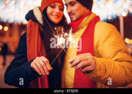 Winter evening, love couple with sparklers outdoor. Man and woman having romantic meeting on city street - Stock Photo