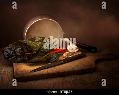 Ruby aka Swiss chard vegetable food preparation, still life with garlic. Chiaroscuro style light painting. Beta vulgaris. - Stock Photo