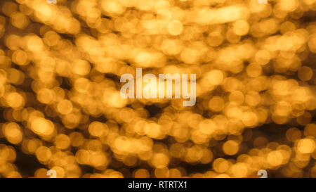 Glistening and shimmering yellow and orange blurred ocean surface at sunset with sun reflections on it - Stock Photo