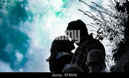 A silhouette of a couple in love kissing in front of the mighty Rhine Waterfalls in Switzerland. - Stock Photo