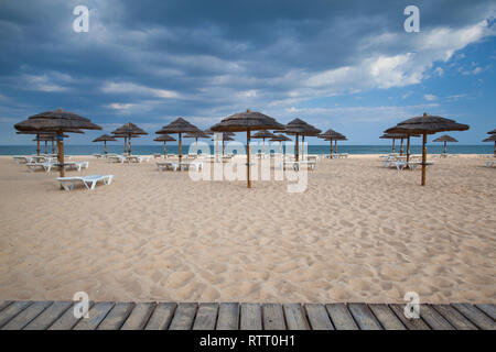 Different parasols and sun loungers on the empty beach on Tavira island, Algarve. Portugal - Stock Photo