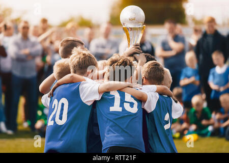 Boys Champion Sport Team. Kids Holding Winner Golden Cup. Children Rising Prize Cup. Boys in Blue Jersey Celebrating Sports Championship - Stock Photo