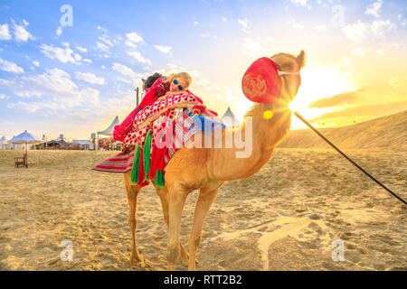 Happy woman lying over a camel on sand dunes of beach at Khor al Udaid in Persian Gulf, southern Qatar. Caucasian tourist enjoys camel ride at sunset - Stock Photo