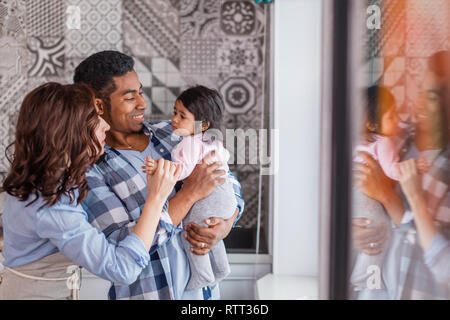 young positive couple playing with their little child at home, love, friendly family concept, copy space