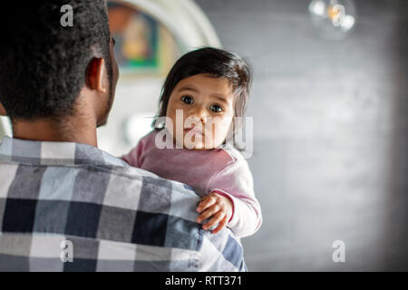 african man in checked T-shirt holding a baby girl, beautiful nice girl looking at the camera, close up photo. childhood. copy space. love, child care
