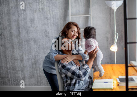 positive parents playing with the baby girl in the modern room, close up side view photo.happy parenthood