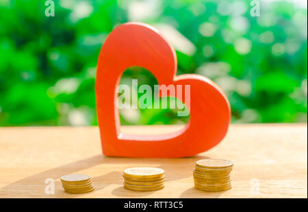 Red wooden heart and money. The concept of saving and accumulation money. Health charity. Donation. The purchases of Valentine's Day. Soft selective f - Stock Photo