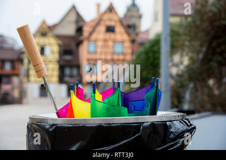 Broken colorful umbrella in garbage can, in front of colorful buildings, Colmar, Alsace, France. - Stock Photo