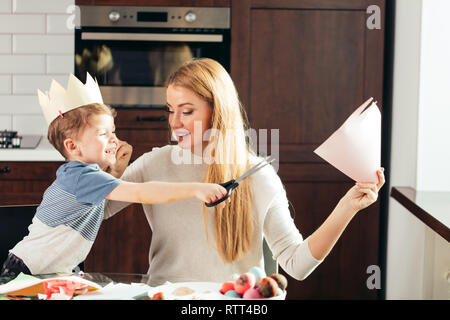 Joyful boy of 4 years-old learning how to use scissors together with a Mom, cutting out the Easter bunny form colourful paper. Happy family sitting at - Stock Photo