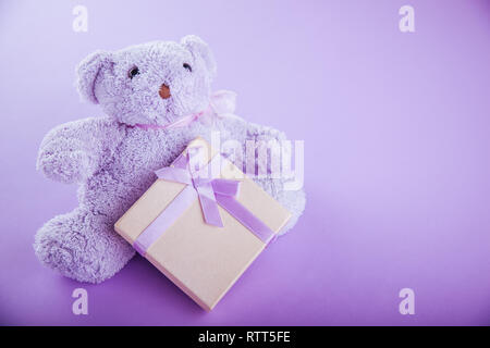 Violet teddy bear with a gift box for Valentines day on purple background - Stock Photo