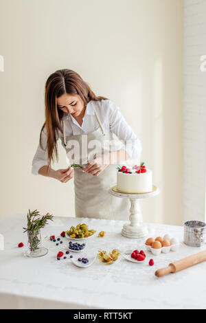 nice girl holding greenery for decorating dessert, close up photo - Stock Photo