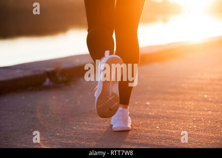 Close up white sneaker of athlete woman runner feet on sunset background - Stock Photo